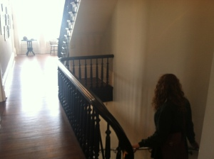 Emilie walks down the sunlight staircase of the historic Jane Addams Hull-House.