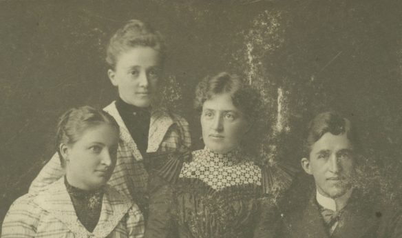 Black and white photograph of three young women and one young man