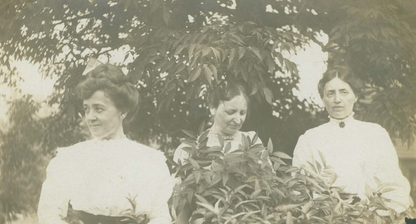 Black and white photograph of three women standing amongst bushes and trees