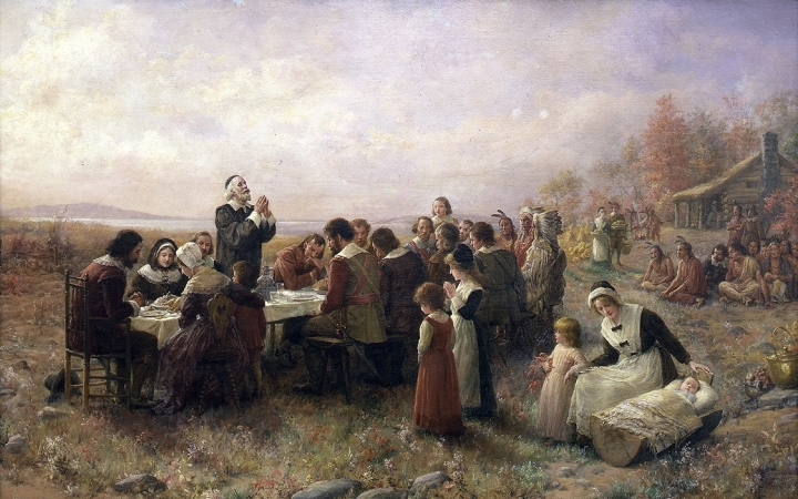 painting of pilgrims and indians sitting down to eat at the first Thanksgiving