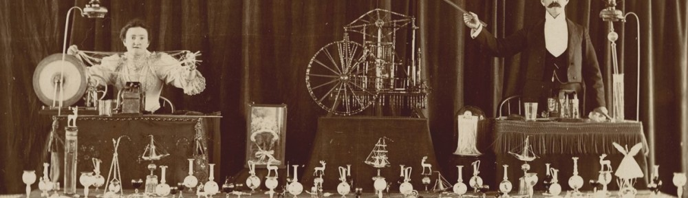 sepia photograph of two itinerant glassworkers behind a table of their goods